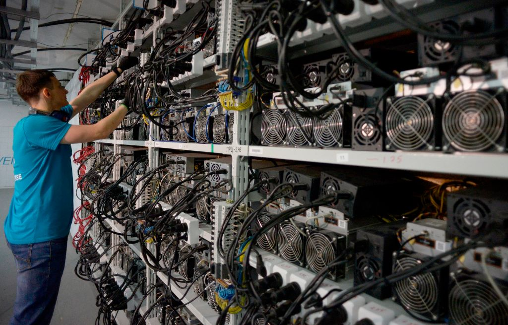 An employee inspects hardware at the CryptoUniverse data centre during a presentation of the largest crypto currency centre in Russia in Kirishi on August 20, 2018. Bitcoin's data centers are many times less efficient than Visa's while processing a meager fraction of transactions. Instead, cryptocurrency's semiconductor and electrical consumption go towards solving a math problem in an effort to win coins issued by the software.