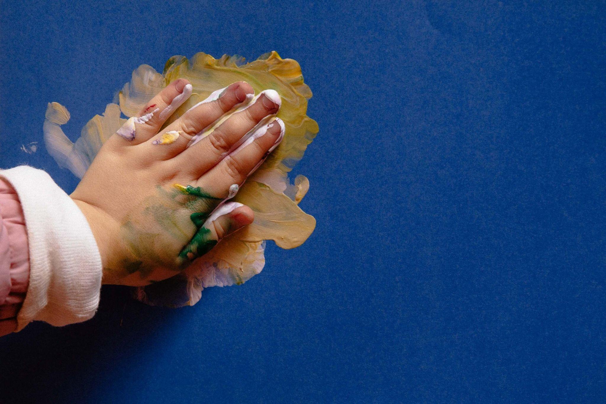 A imagem mostra a mão de uma criança suja de tinta carimbando uma parede azul.