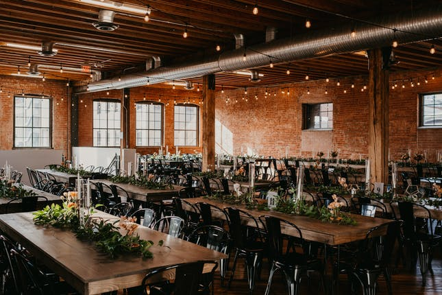 wedding venue with chairs empty and hanging lights. Surrounded by brick walls