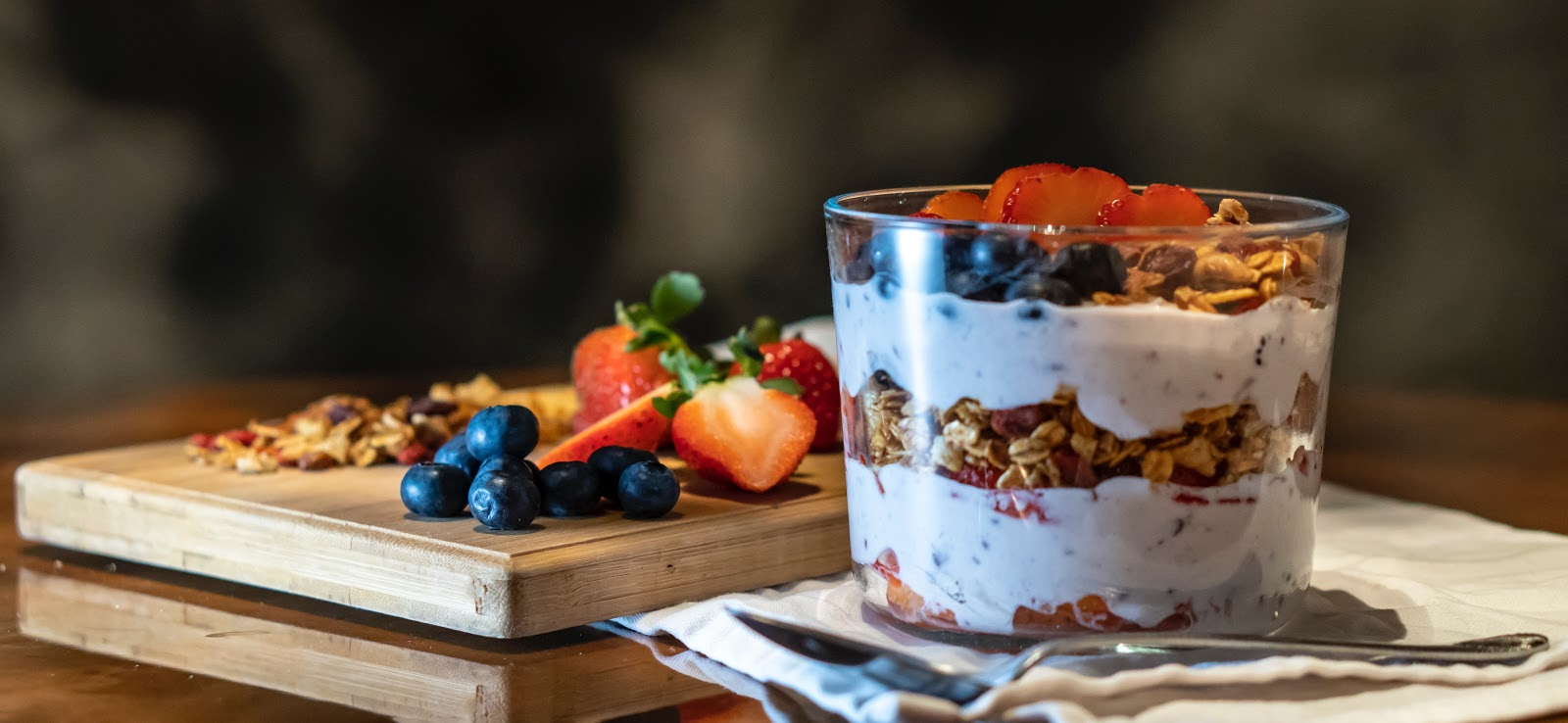 Yogurt serving in a cup with sliced fruits on a cutting board.
