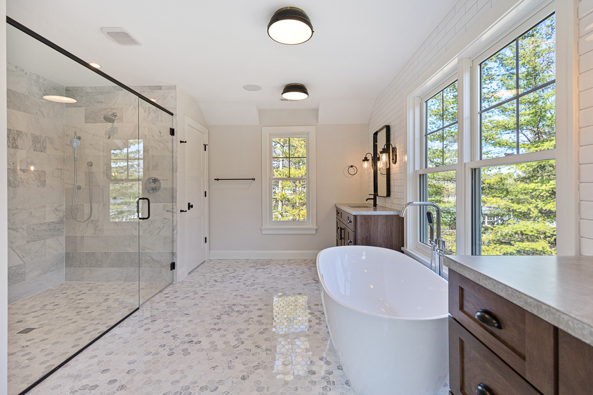 Luxury bath with large picture windows delivering ample natural light, featuring a walk-in, barrier free shower, a stand-alone tub and two individual vanities.