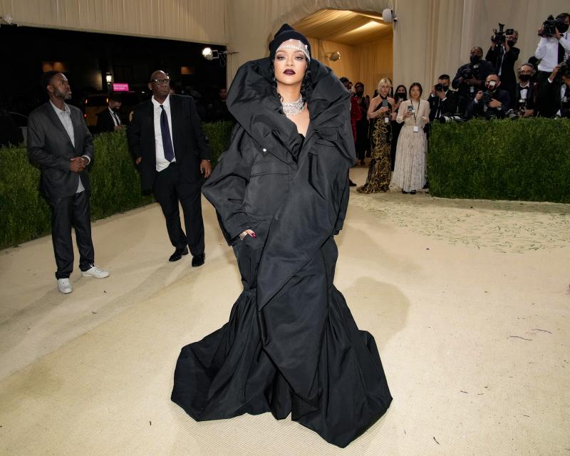 Mulher preta usa vestido preto volumoso com camadas e dobras cobrindo todo o corpo, tem o cabelo preso com acessório também preto. Foto: Getty Images. Post Looks icônicos do VMA e Met Gala 2021.