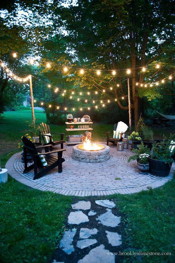 outdoor fire pit and seating with string lights and bar station