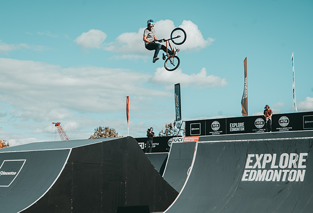 "BMX rider turning a trick in the air on his bike above ramps that say ""Explore Edmonton"""