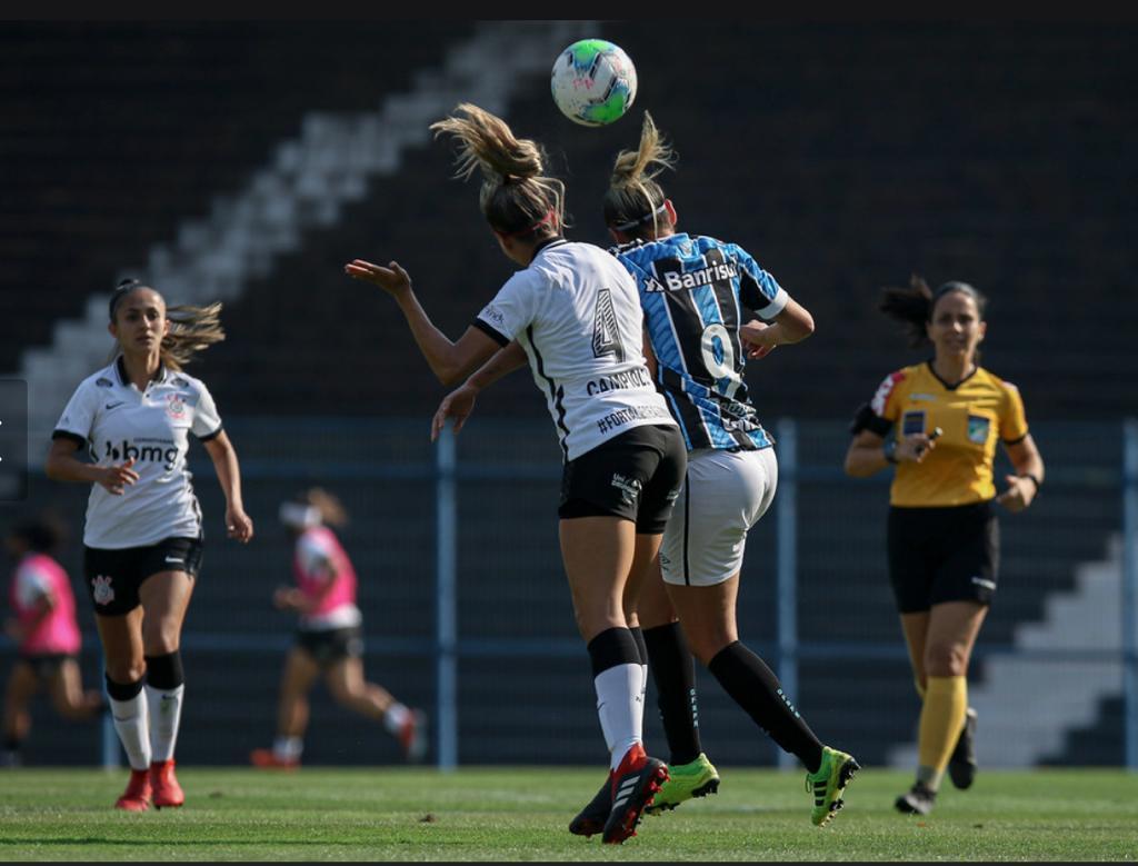 Mulher jogando futebol de campo e pessoas por trásDescrição gerada automaticamente