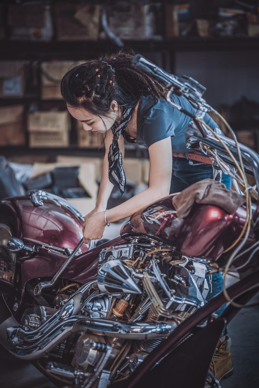photo of woman repairing motorcycle