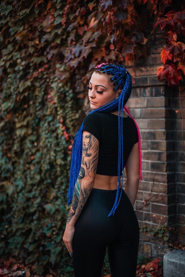 Mulher posando de costas com o braço coberto com tatuagens e um cabelo trançado colorido. Meio azul e meio rosa.