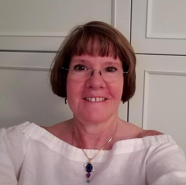 TOCTooler Jaci Collins smiling at the camera, wearing a boatneck white blouse, drop earrings, and a large pendant