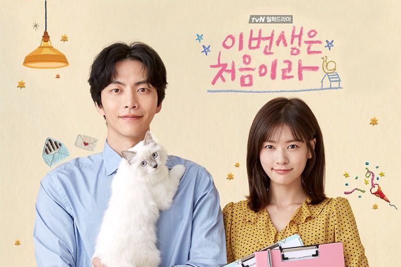 Banner de divulgação de Because This Is My First Life. Exibe os dois protagonistas, um homem e uma mulher, vestidos com roupas sociais. A mulher, na direita, carrega pranchetas, e o homem, na esquerda, carrega um gato.