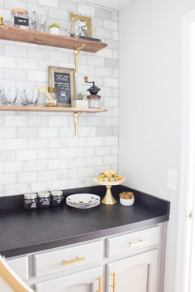 modern coffee bar with tile backsplash and black countertops, complemented by light grey wall paint and small wooden shelves with gold accents