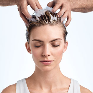 A woman having shampoo massaged into her hair