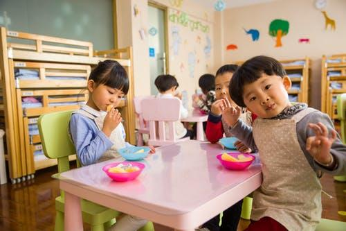 Three Toddler Eating on White Table