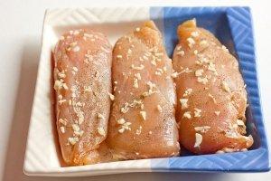 Чеснок измельчаем, натираем им и небольшим количеством чёрного молотого перца просоленные куриные грудки.