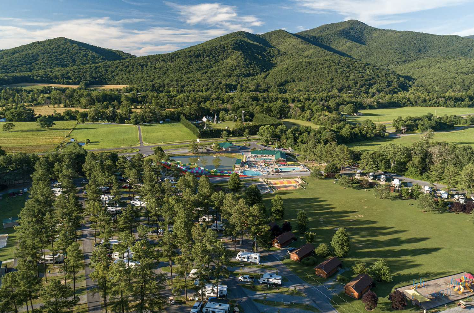 Mountains in the background with aerial view of the campground, RVs, cabins and pool area.