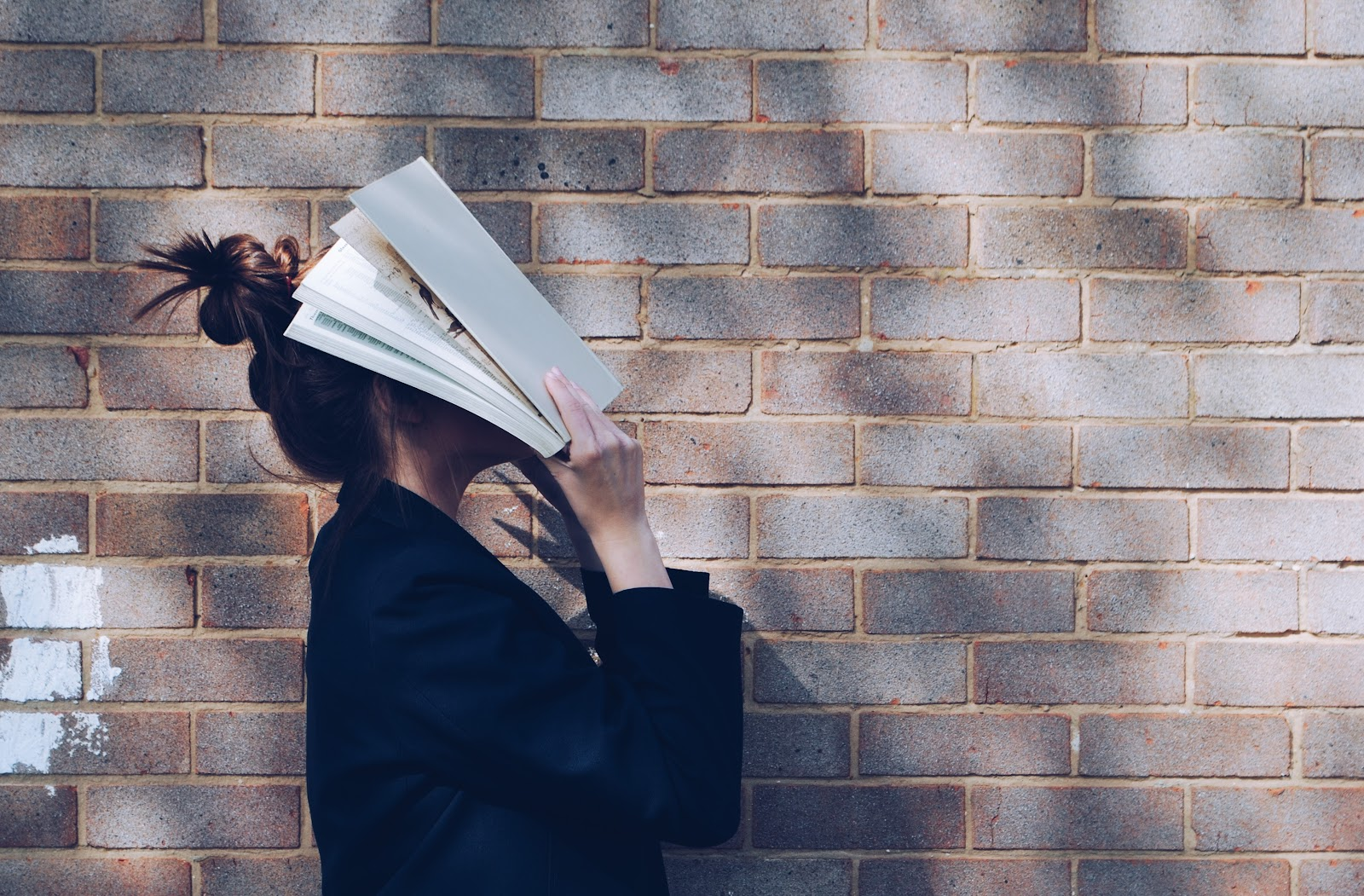 A person buries their head into a book in front of a wall