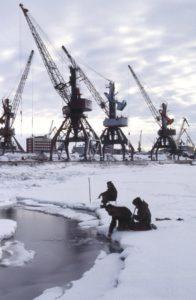Three Russian fishers fishing on a cloudy day in icy frozen water with industrial plants in background in Krasnoyarsk Krai, Russia, Siberia