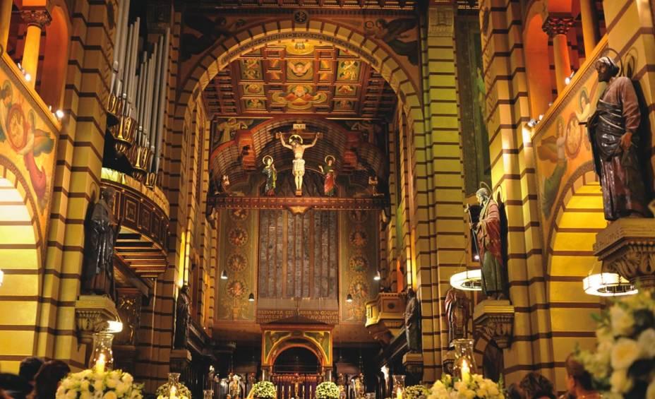 Igreja de São Bento toda decorada com santos (em todos os lados), imagens e flores.