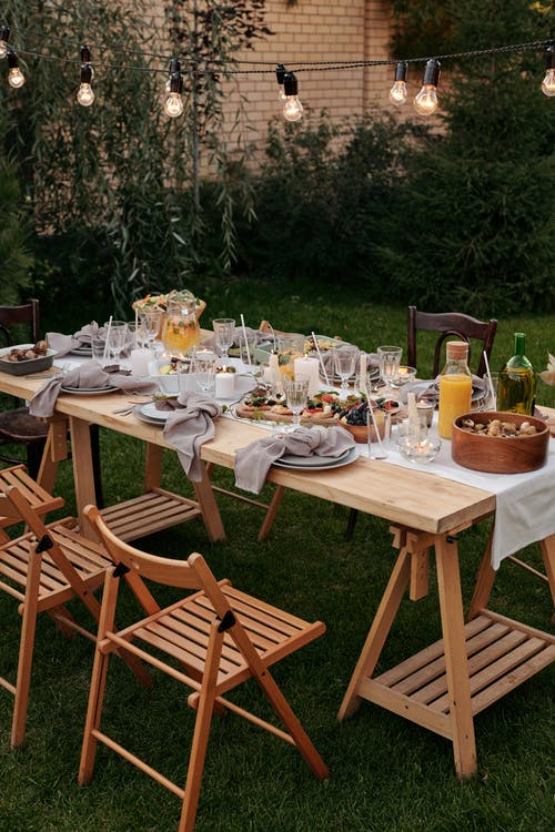 Food on Brown Wooden Table With Chairs and Plates