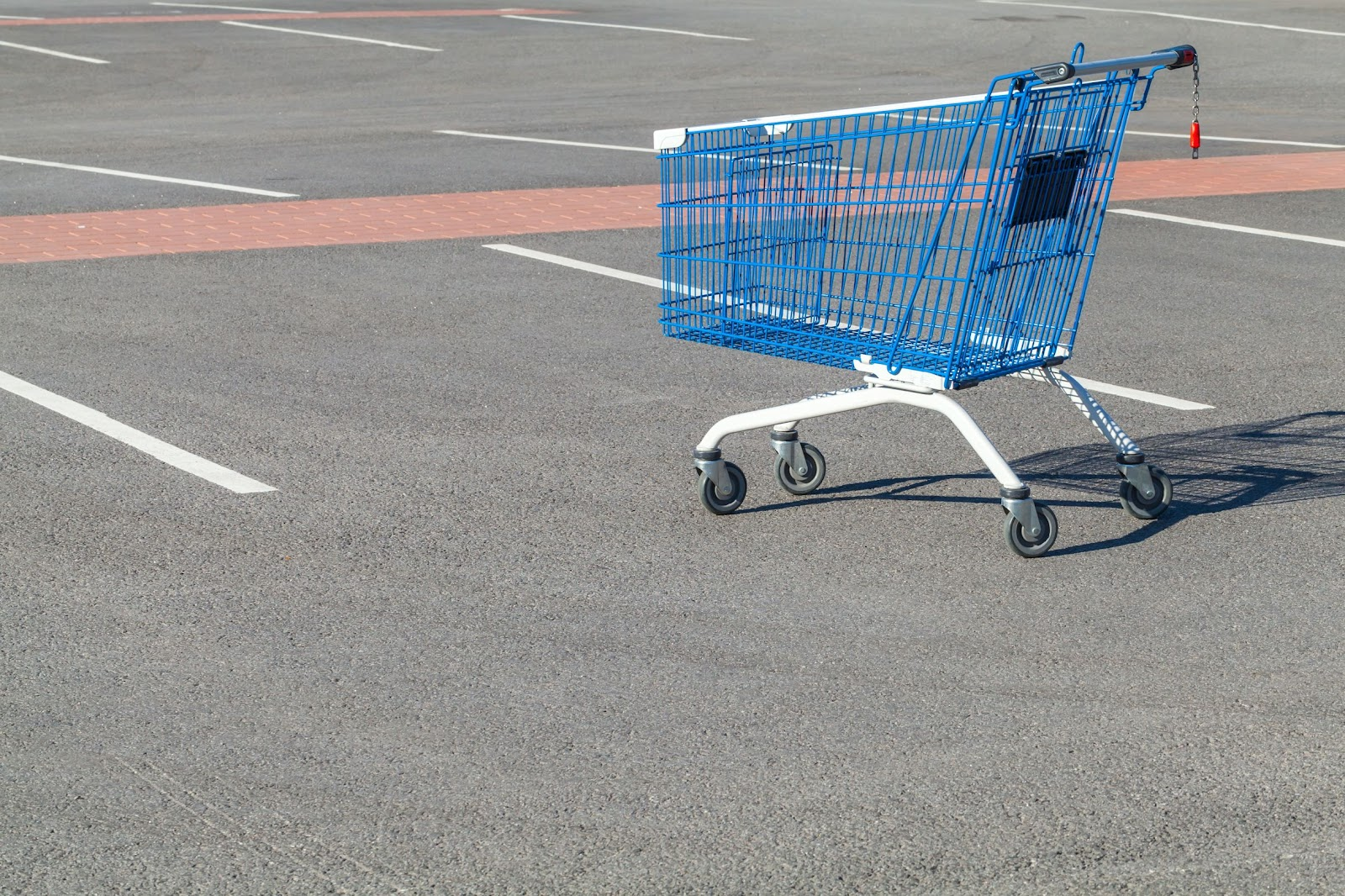 Abandoned shopping cart in an empty parking lot symbolizing potential e-commerce purchases
