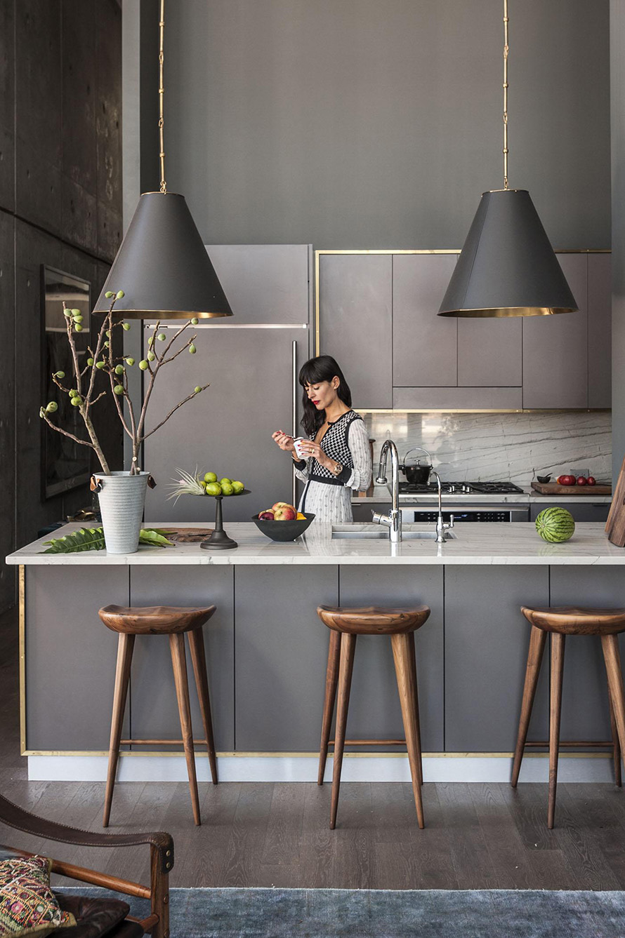 modern grey kitchen with gold accents wood bar stools and marble countertops