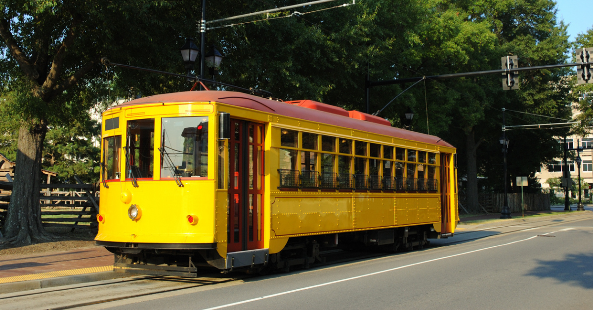 A yellow streetcar in the street