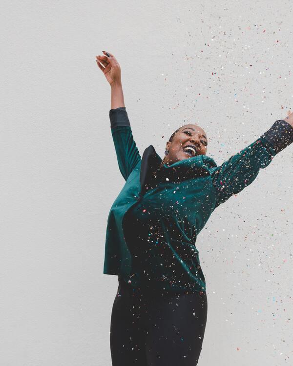 foto de uma mulher negra alegre e comemorando com papéis coloridos caindo em cima dela