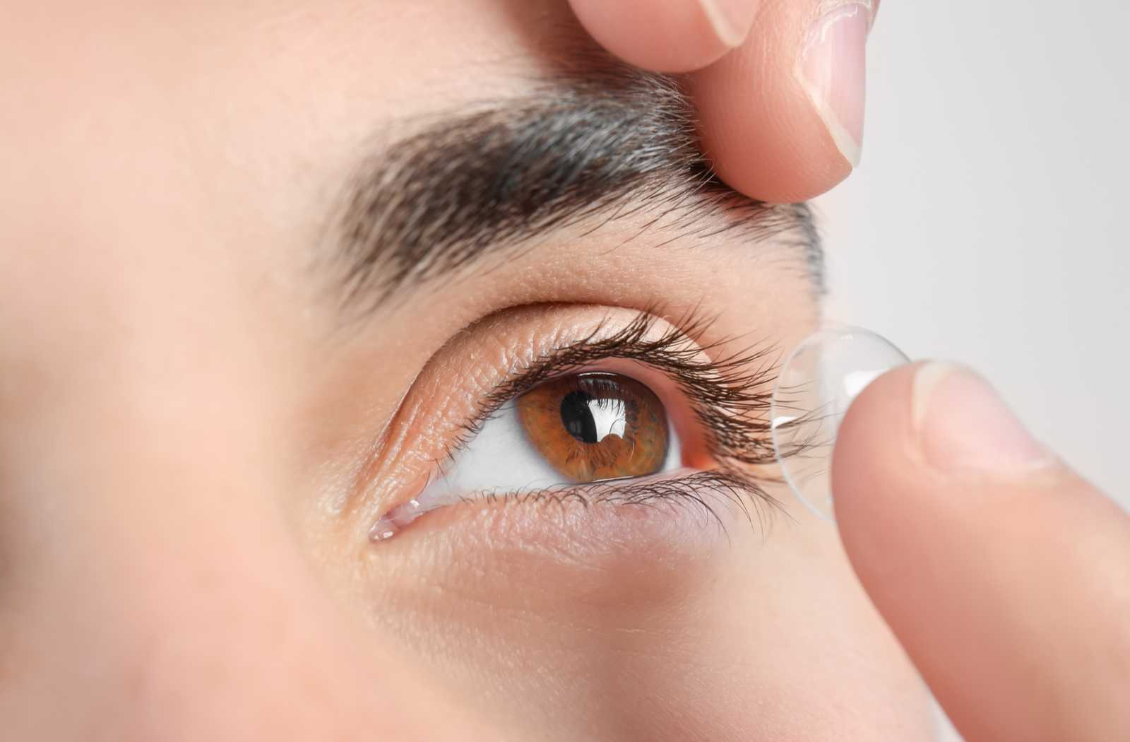 contact lenses applied by optimistic person in extreme closeup