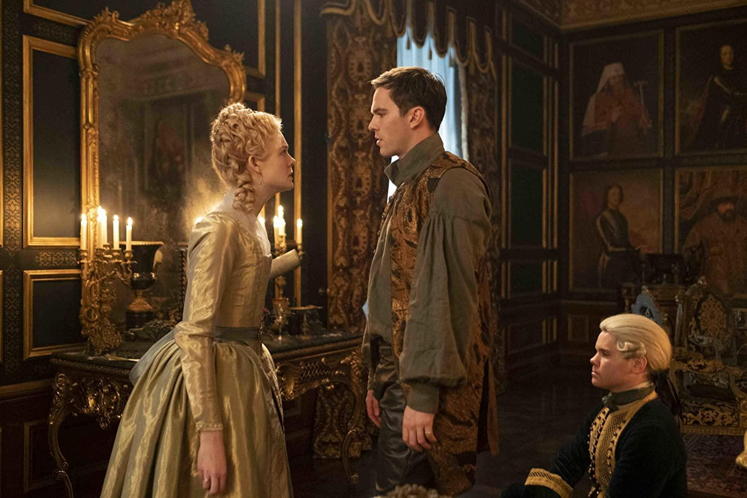The Great (2020). Catherine, this time in a shiny yellow-gold dress with long sleeves, addresses Peter (Nicholas Hoult) with an angry expression. Peter is a young white man with short brown hair, wearing a khaki coloured shirt with billowing sleeves and a bronze waistcoat. They are in an elaborate palace room with large oil painting portraits and gilded mirrors adorning the walls. A young footman with a white wig and black and gold uniform kneels on the ground beside Peter, subservient.
