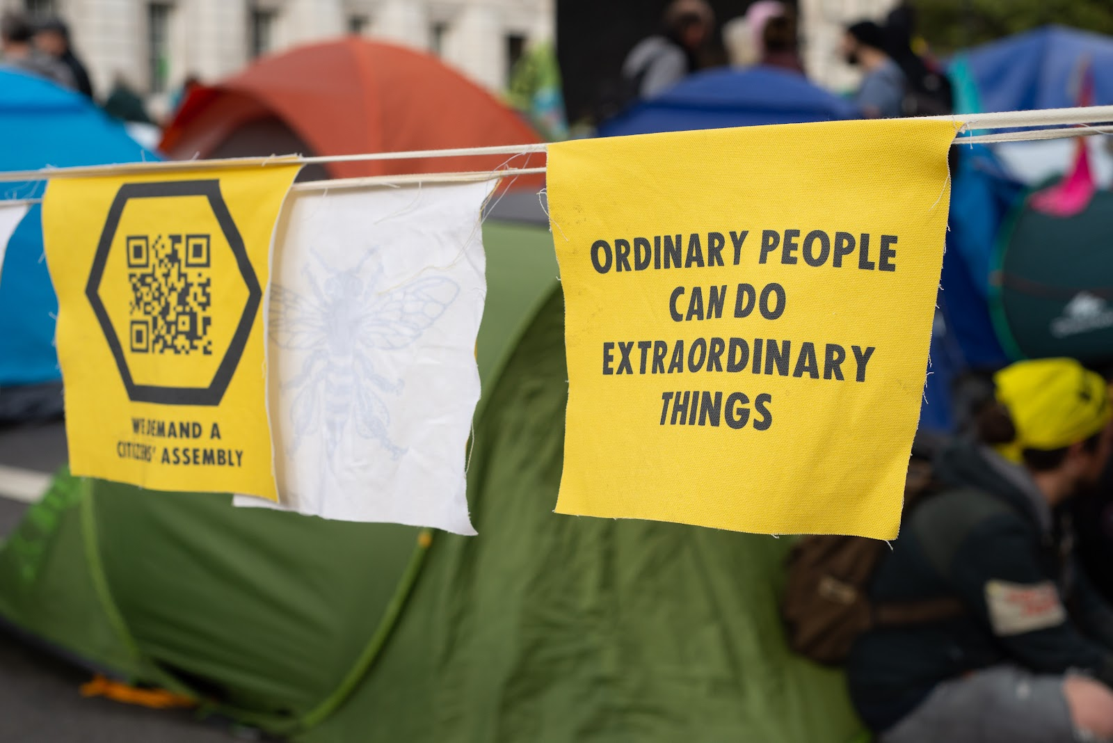 "Bunting printed with ""Ordinary people can do extraordinary things"", with a rebel tent camp behind"