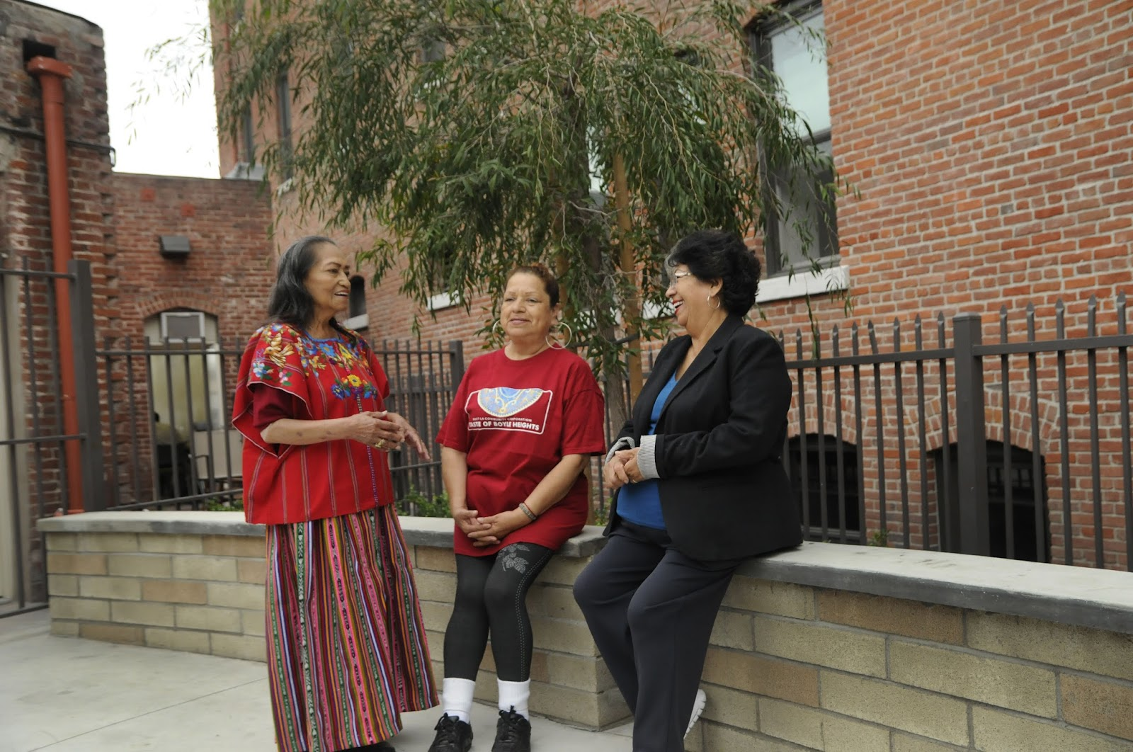 Three women in front of a brick building.