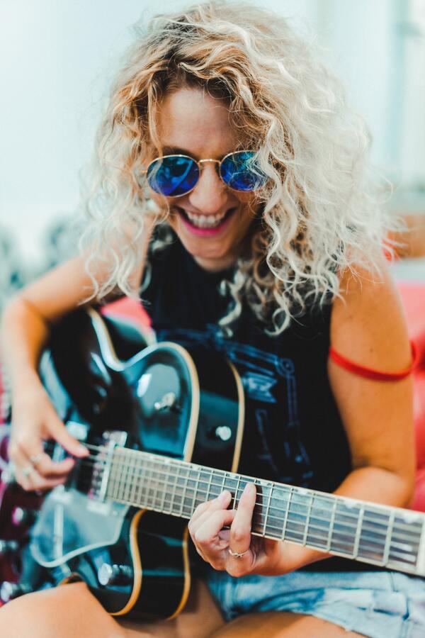 Foto de uma mulher loira, rindo e tocando violão