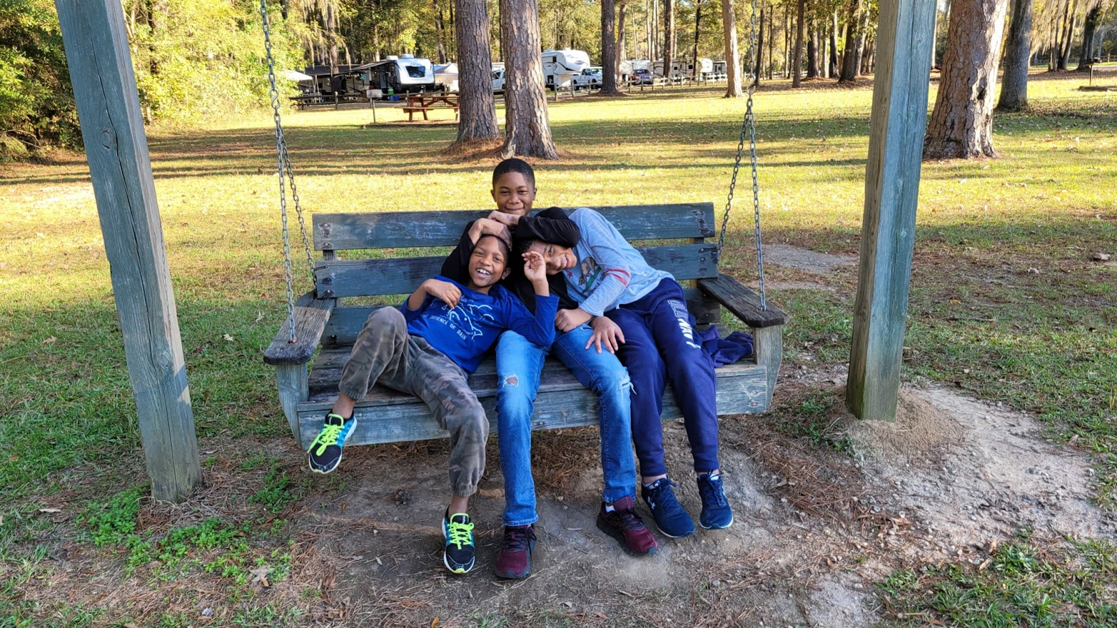 Three brothers sit together on a bench swing