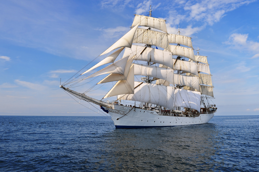 Tall ship in full sail with sails furled.