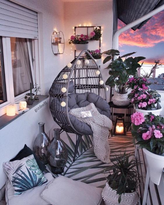 Varanda em estilo romântico com cadeira de balanço decorada, vasos de flores e bastante iluminação.
