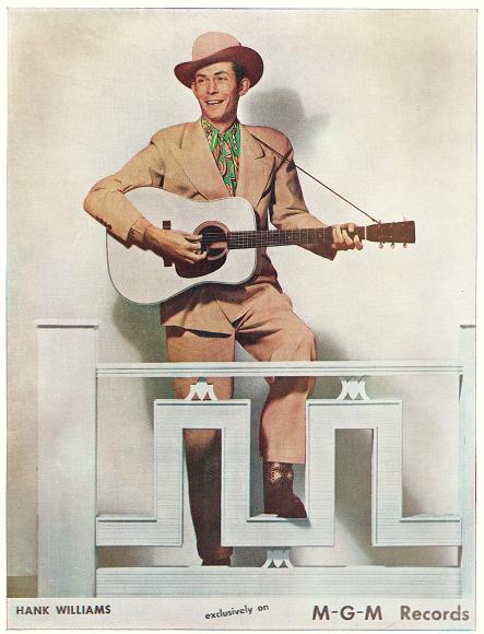 Hank Williams posing while holding the guitar.