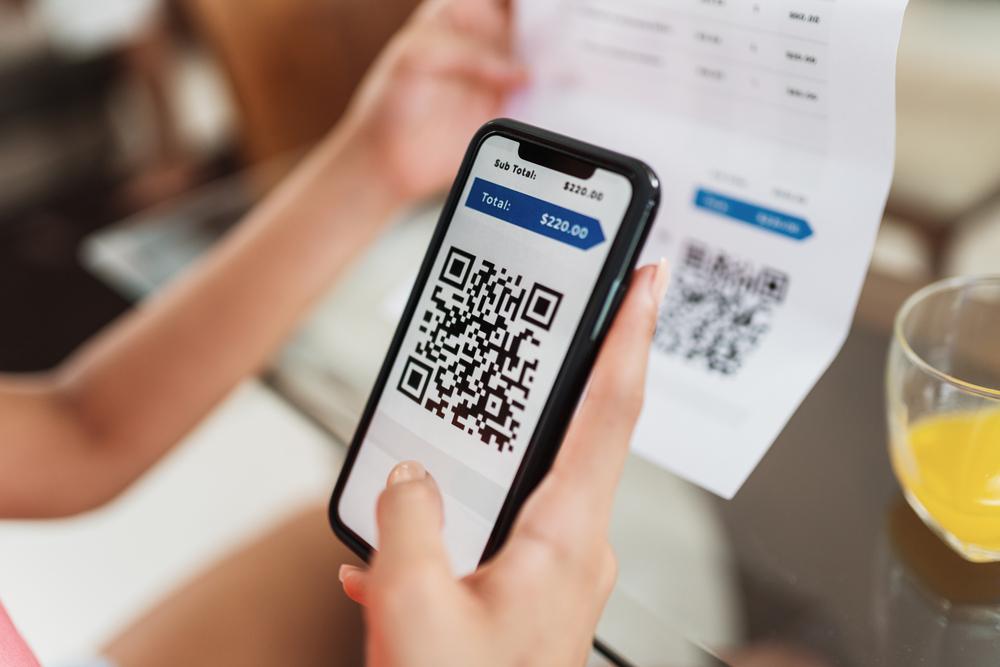 Mulher segurando celular com leitor de QR Code pagando conta