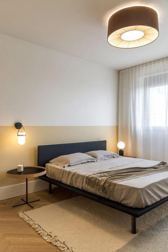 Quarto com cama de casal e parede com técnica de pintura de meia parede, piso de madeira e mesinha de canto redondo.