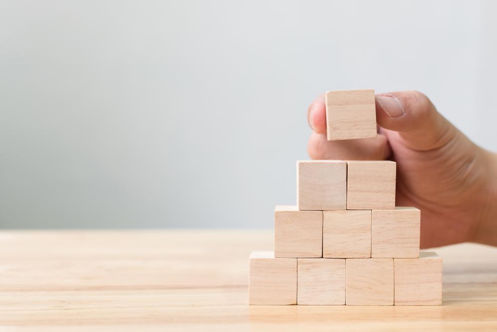 Uma mão colocando a última peça de uma pirâmide de cubos.