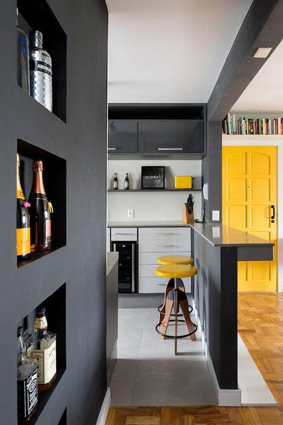 Apartamento com porta de entrada amarela e cozinha com móveis cinza, piso em tom neutro com bancos e acessórios amarelos.
