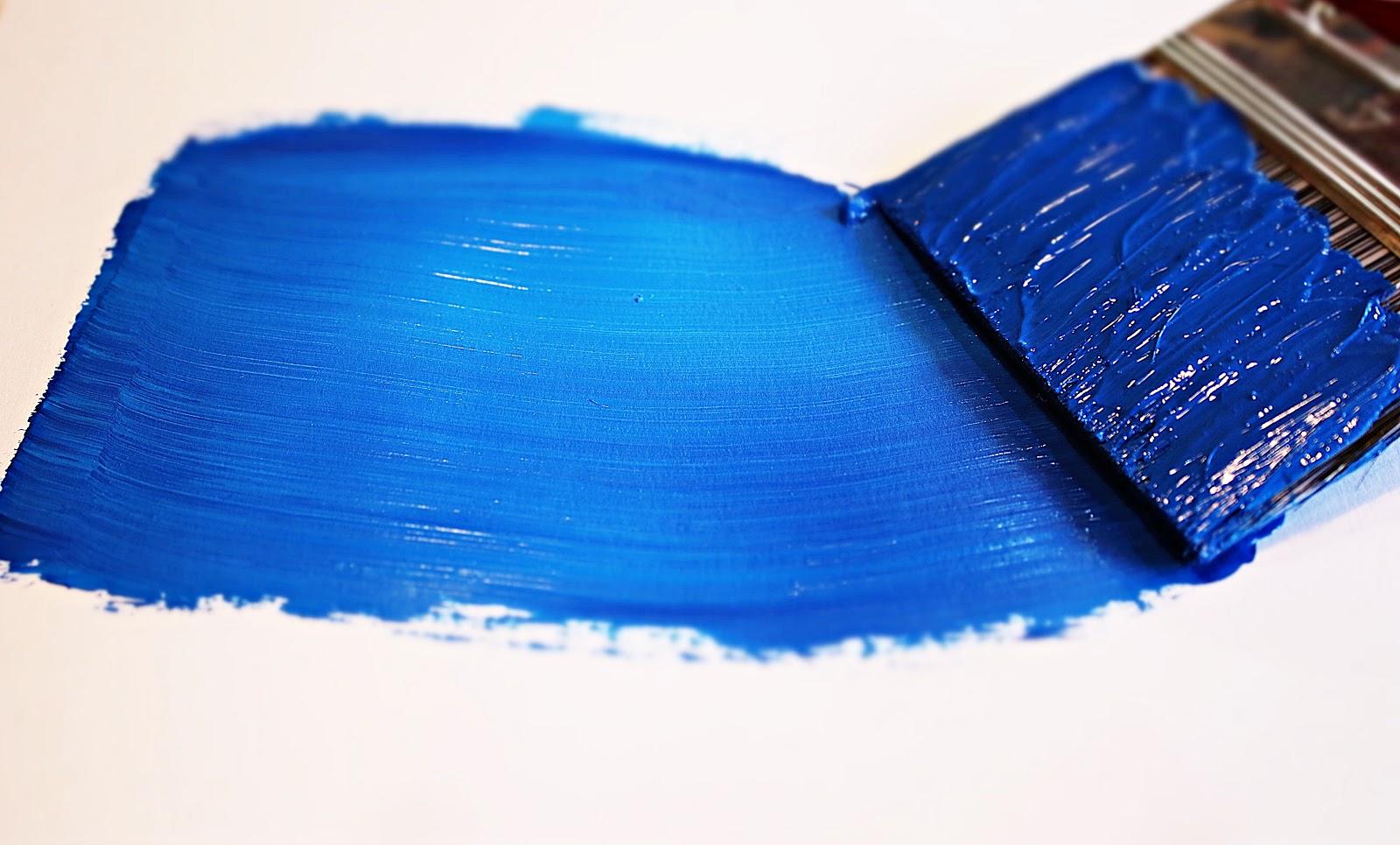 A paintbrush spreads blue paint across a bare white medium.