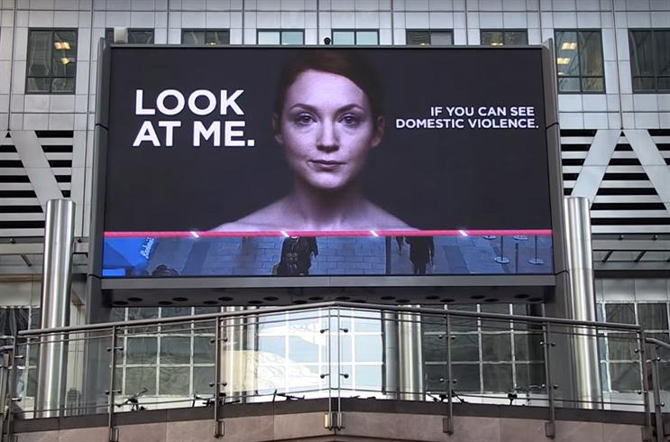 "Billboard with a woman's face that says ""Look at me. If you can see domestic violence."""