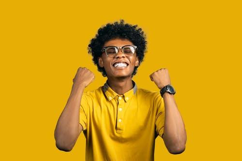 Pria Afrika-Amerika yang bersemangat dengan aksesori yang menunjukkan gerakan ya