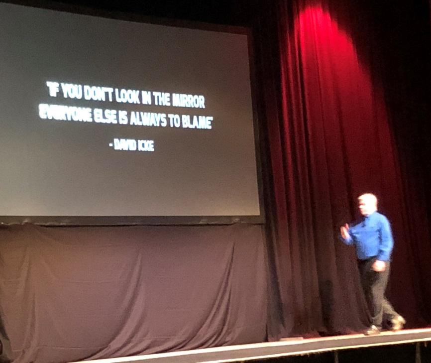 """David Icke on stage in Southport with a slide that says """"If you don't look in the mirror everyone else is always to blame"""" - the quote is attributed to David Icke."""