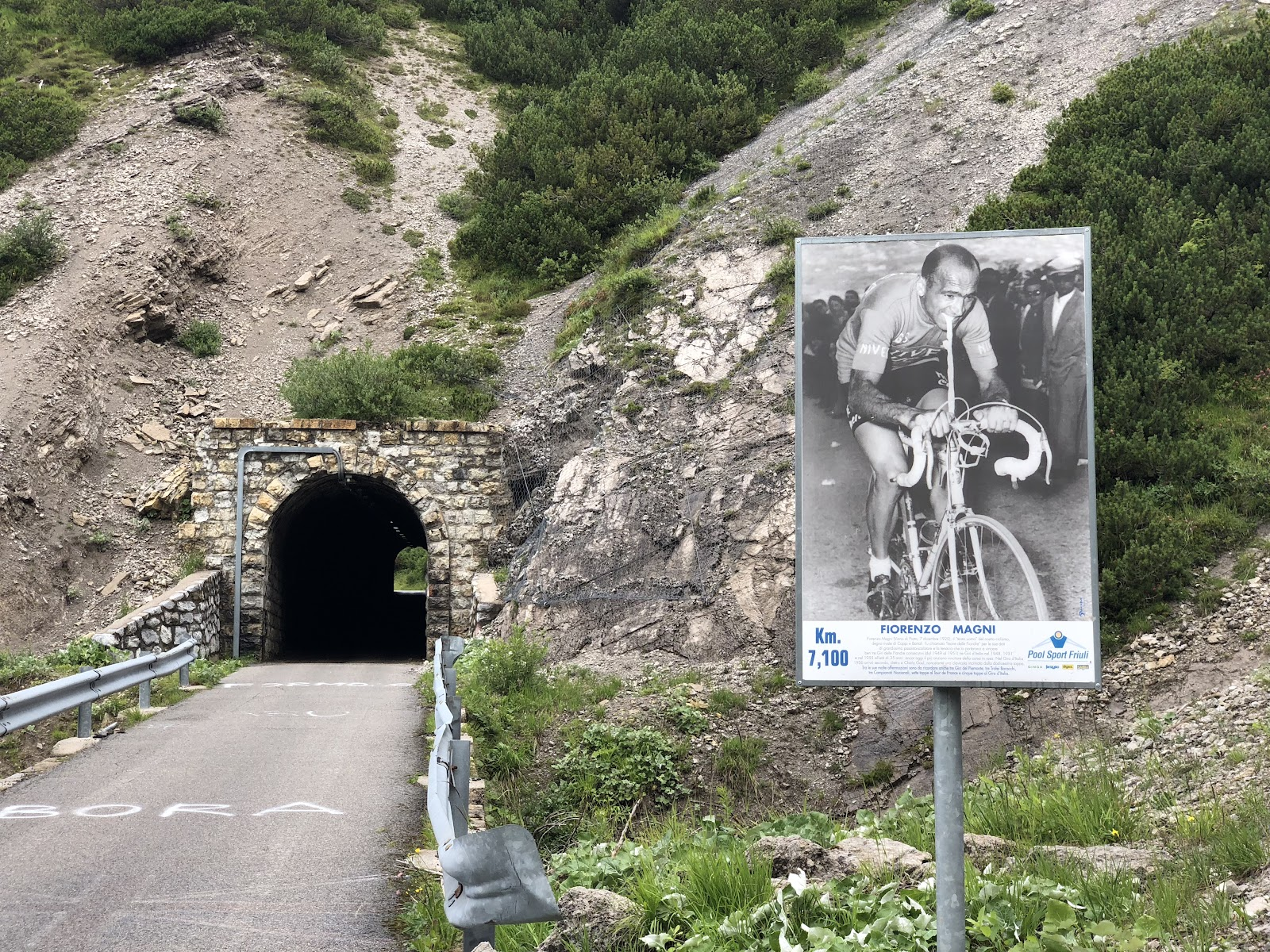 Climb Monte Zoncolan from Ovaro by bike - tunnel, sign, km sign, road