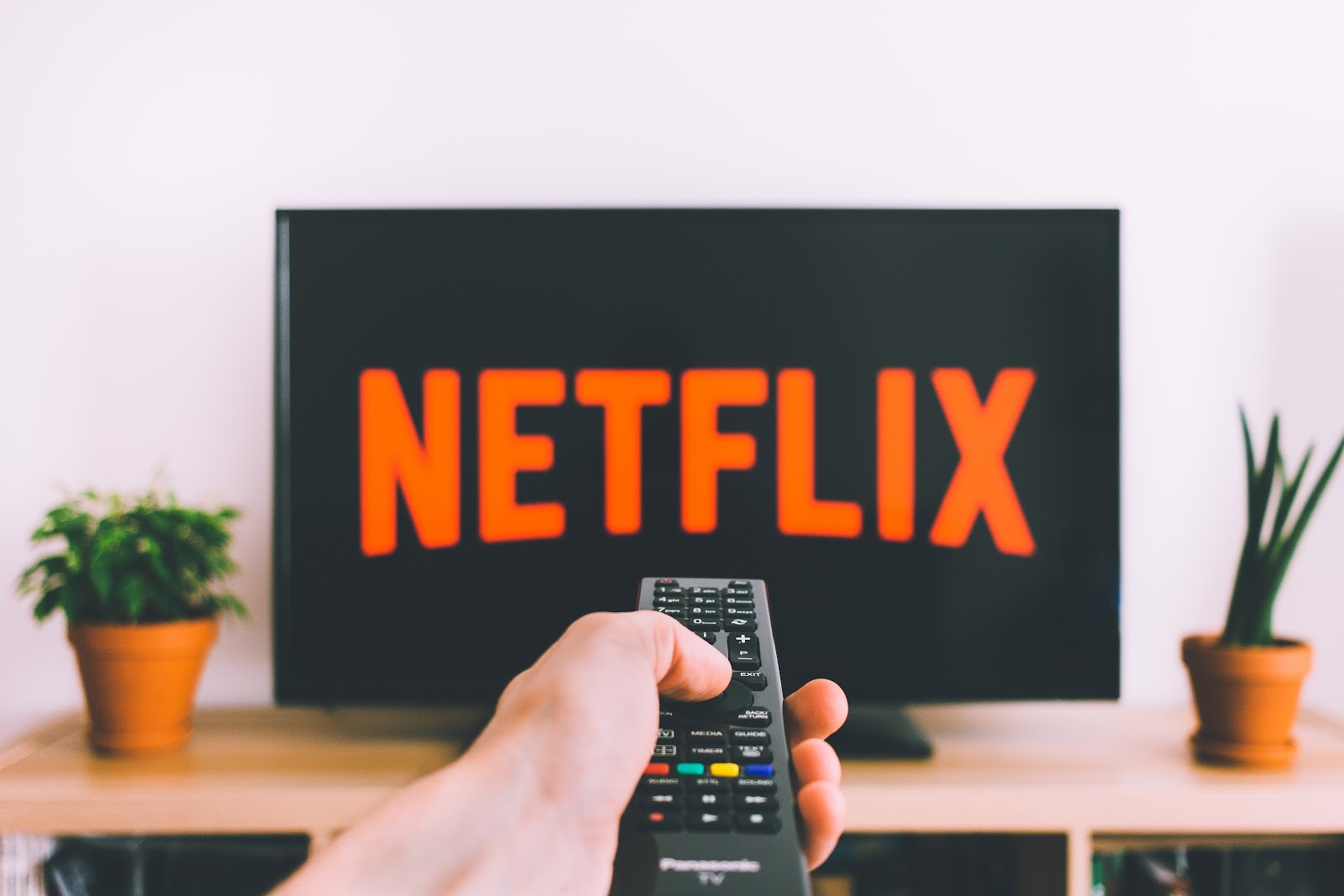 A hand pointing a remote at a tv displaying the Netflix logo