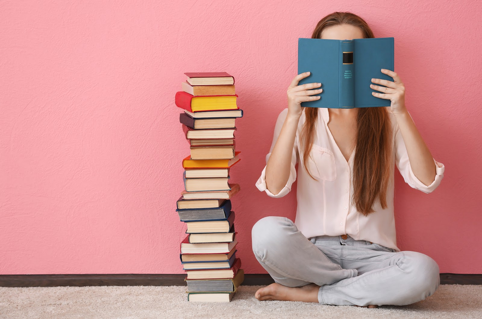 Young woman sitting next to a pile of books, reading