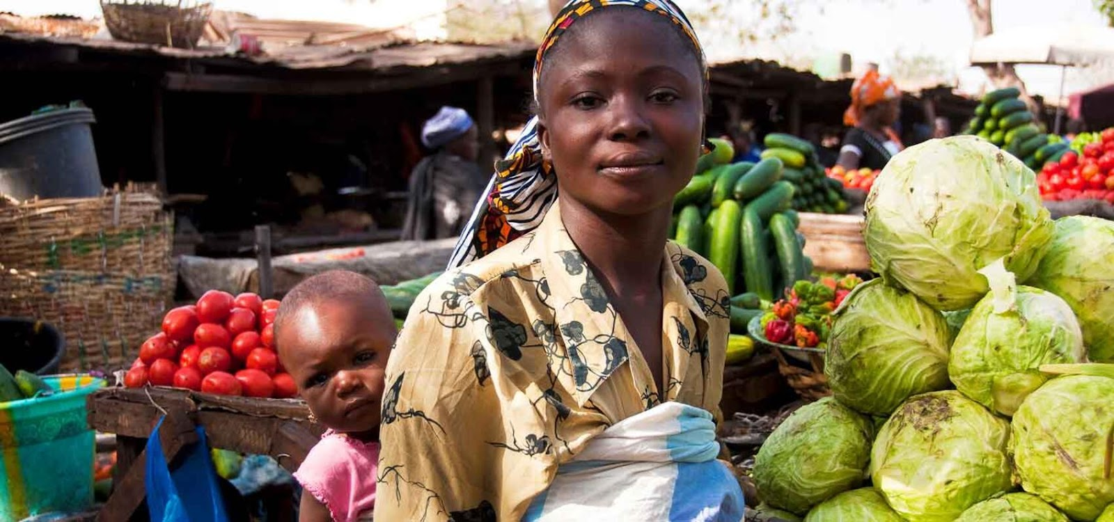 An African youth in a market, standing in front of a vegetable stand with a baby on their back.