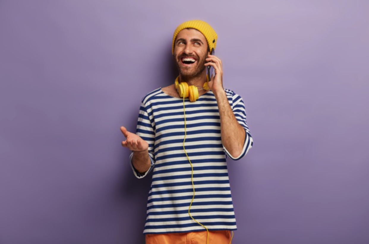 Man in striped t-shirt talking on phone | Influencer Marketing for Shopify Merchants