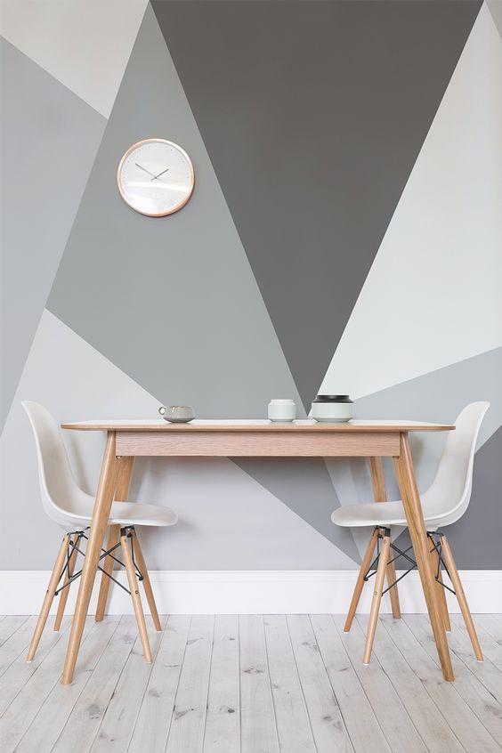 Ambiente com parede geométrica em tons de cinza, mesa de madeira com duas cadeiras brancas e piso de madeira.