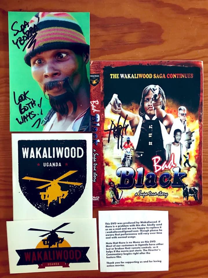 Deuvedé, carátulas de Wakaliwood con helicópteros y una foto del actor ugandés Bruce U dedicada a nuestro socio Juan Yborra.
